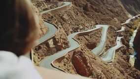 Panoramic view of windy mountain road in the Dades Gorge, Gorges Du Dades, Morocco, point of view from woman back, full