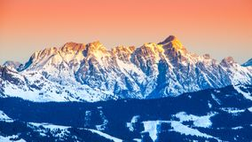 Panoramic view of winter mountains. Alpine peaks covered by snow and illuminated by rising sun.  Stock Photos