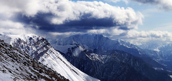 Panoramic view on winter mountains in evening and cloudy sky Stock Photos