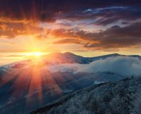Panoramic view of winter mountains at sunrise. Landscape with foggy hills and trees covered with rime. Royalty Free Stock Photo