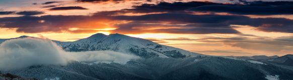 Panoramic view of winter mountains at sunrise. Landscape with foggy hills and trees covered with rime. Dramatic cloudy over sky Stock Image