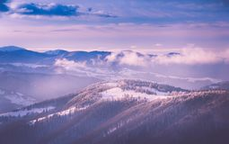Panoramic view of winter mountains at sunrise. Landscape with foggy hills and trees covered with rime. Happy New Year! Filtered image:cross processed retro Royalty Free Stock Images