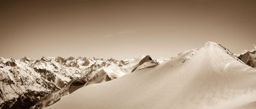 Panoramic view on winter snow mountain. Caucasus Mountain, region Dombay. Slope for freeriding, top of Musa Achitara. Sepia toned landscape Royalty Free Stock Photo