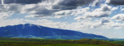 Wyoming Vast Landscape under dark clouds. Panoramic view of Wyoming`s ominous cloudy skies over open fields and sections of the Laramie Mountain Range, seen from Royalty Free Stock Images