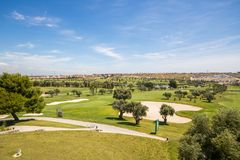 Panoramic views of golf course with sandpit, lake, trees and buggies royalty free stock photo