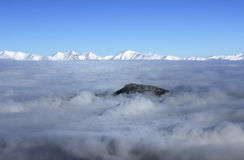 Panoramic views of the mountains. Snowy mountains covered with clouds clear day Royalty Free Stock Image