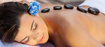 Woman Relaxing At Health Spa Having Hot Stone Treatment Massage royalty free stock photography