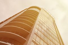 Panoramic wide angle view to steel light gold background of glass high rise building skyscraper with balconies Royalty Free Stock Photography