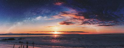 Panoramic winter landscape in sunrise with double exposure night sky landscape. D royalty free stock image