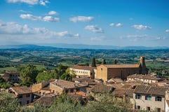 Panoramica dei tetti e della chiesa con le colline verdi ed il cielo blu a San Gimignano Fotografie Stock Libere da Diritti