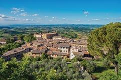 Panoramica dei tetti e della chiesa con le colline verdi ed il cielo blu a San Gimignano Immagine Stock Libera da Diritti