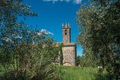 Panoramica della chiesa e del campanile con gli alberi intorno nel villaggio di Monteriggioni Immagini Stock
