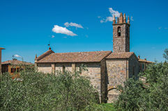 Panoramica della chiesa e del campanile con gli alberi intorno nel villaggio di Monteriggioni Fotografia Stock Libera da Diritti