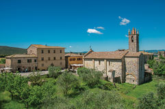 Panoramica della chiesa e del campanile con gli alberi intorno nel villaggio di Monteriggioni Immagini Stock Libere da Diritti