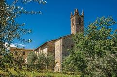 Panoramica della chiesa e del campanile con gli alberi intorno nel villaggio di Monteriggioni Fotografie Stock