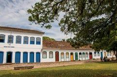 Panoramica della via del ciottolo con le vecchie case e di grande albero in Paraty Fotografia Stock Libera da Diritti
