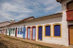 Panoramica della via del ciottolo con le vecchie case sotto il cielo nuvoloso blu in Paraty Fotografie Stock