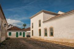 Panoramica della via del ciottolo con le vecchie case sotto il cielo soleggiato blu in Paraty Fotografia Stock Libera da Diritti