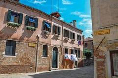 Panoramica delle case antiche e dei vestiti che appendono in un vicolo a Venezia Immagini Stock