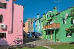 Panoramica delle case a terrazze variopinte, del balcone e dei vestiti appendenti in un vicolo in Burano Fotografia Stock Libera da Diritti