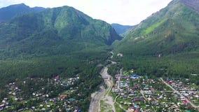 Panoramica di bello paesaggio Il volo del fuco sopra il villaggio, situato nelle montagne Vista dell'occhio del ` s dell'uccello stock footage
