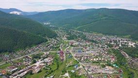 Panoramica di bello paesaggio Il volo del fuco sopra il villaggio, situato nelle montagne Vista dell'occhio del ` s dell'uccello video d archivio