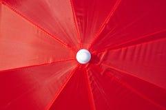 Panoramica di un ombrello di spiaggia rosso Immagine Stock Libera da Diritti
