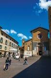 Panoramica di un quadrato con le costruzioni, la chiesa e la gente anziane sotto un cielo blu in Orvieto Fotografia Stock Libera da Diritti
