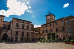 Panoramica di un quadrato con le vecchi costruzioni, torre di orologio e negozio in Orvieto Fotografia Stock Libera da Diritti