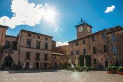 Panoramica di un quadrato con le vecchi costruzioni, torre di orologio e negozio in Orvieto Immagini Stock Libere da Diritti