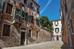 Panoramica di vecchie costruzioni di mattone in un vicolo con il cielo soleggiato blu a Venezia Fotografia Stock