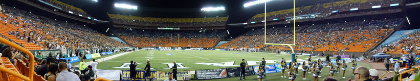 Panoramico del campo di football americano della partita di football americano dell'istituto universitario alla notte d Immagini Stock Libere da Diritti
