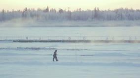 Panoramicznego widoku Śnieżna dolina z Chodzącymi mężczyzna przeciw zmierzchu niebu zdjęcie wideo