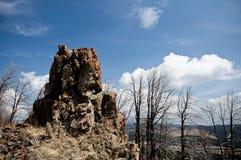 Panoramiczni widoki samotna skała wśród białych chmur Obrazy Royalty Free