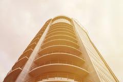 Panoramiczny szeroki kąta widok stali światła złocisty tło szklany wysoki wzrosta budynku drapacz chmur z balkonami Obrazy Stock