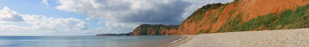 Panoramiczny widok falezy przy Sidmouth w Devon, pokazywać kamiennego brzeg i utleniać falezy w zatoce fotografia stock
