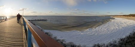 Panoramiczny widok most, piaskowata plaża pod śniegiem i lodowe fale morze bałtyckie na słonecznym dniu w Palanga, Lithuania zdjęcia royalty free
