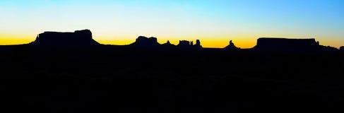 Panoramisch de zonsopgangsilhouet van de Monumentenvallei, de Natiepark van Navajo Stock Fotografie