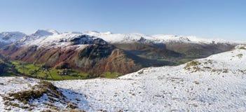 Panoramisch vom schneebedeckten Boden vorbei zu Schnee-mit einer Kappe bedeckten Bergen Stockfotografie