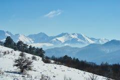 Panoramische Ansicht der Berge Im Vordergrund gibt es eine schneebedeckte Lichtung, auf der Mitte ein Wald, auf der weit Klippe,  stockfoto