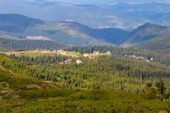 Panoramische bergenmening met dorp en schaduw van wolken op groene bosvallei Karpatische bergen in perspectief royalty-vrije stock fotografie