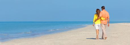 Panoramische Fahnen-Paare, die auf einen leeren Strand gehen stockfoto
