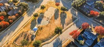 Panoramische hoogste menings woonspeelplaats met kleurrijk dalingsweiland stock foto