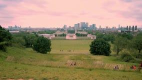 Panoramische horizonmening van Greenwich en nationale maritieme museum en wolkenkrabbers van Canary Wharf bij zonsondergang - Lon stock video