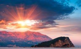 Panoramische Landschaft der Küste Budva Riviera: Insel und Berge Sveti Nikola bei Sonnenuntergang Stockfoto