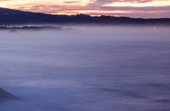 Panoramische landschapsmening na zonsondergang op Atlantische kustlijn in roze hemel met reusachtige golven, Baskisch land, Frank stock fotografie