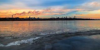 Panoramische Szene mit gefrorenem See und Fabrik im Hintergrund lizenzfreie stockfotos