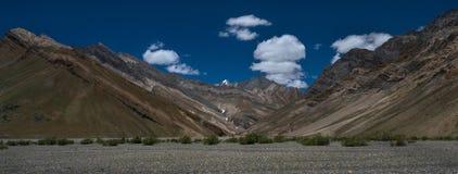 Panoramisches Fotohochgebirge des Tales von Zanskar-Fluss, schöne Gebirgsketten, Kieselunterseite des Flusses zum foregr Lizenzfreies Stockfoto