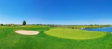 Panoramy pola golfowego bujny trawa Na jeziorze Zdjęcia Royalty Free