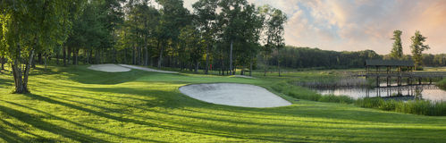 Panorarmic view of golf green with traps and trees. Panoramic view of a golf green in late afternoon sunlight with sand traps, trees and water Royalty Free Stock Image